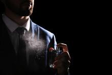 Man Spraying Luxury Perfume On Black Background, Closeup