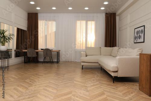 Fototapeta Modern living room with parquet flooring and stylish furniture