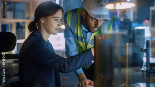Fotografia, Obraz Modern Factory Office: Male Project Manager Talks to a Female Industrial Engineer who Works on Computer