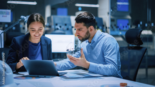 Industry 4.0 Modern Factory Meeting Room: Chief Engineer Holds Mechanism, Shows it to Female Designer, They Talk. Scientists in Contemporary Lab Build Electronic Machinery for With Futuristic Design