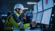 Industry 4.0 Modern Factory: Facility Operator Controls Workshop Production Line, Uses Computer with Screens Showing Complex UI of Machine Operation Processes, Controllers, Machinery Blueprints