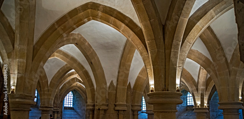Arched ceiling vaults with columns or pillars with windows in the background in the Wells Cathedral in Wells, Somerset, England.