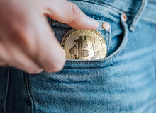 Close Up Footage Of Man's Fingers Putting The Bitcoin Coin In The Blue Jeans Small Pocket. Savings, Digital Currency, Cryptocurrency, Investing, And Smart Outgoings Managing Concept.
