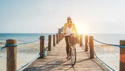 Portrait of a happy smiling woman dressed in light summer clothes and sunglasses riding a bicycle on the wooden sea pier and looking at camera. Careless vacation in tropical countries concept image