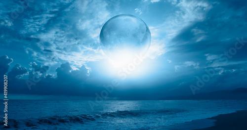 Obraz na płótnie Full glass moon (or crystal ball moon) rising over empty sea with beach at night