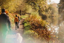 Family Walking Along Path By Canal In Fall