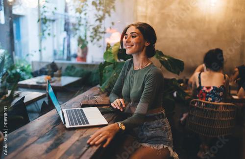 Obraz Cheerful woman working on laptop in cafe - fototapety do salonu