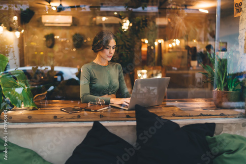Obraz Positive woman working on laptop in creative cafeteria - fototapety do salonu