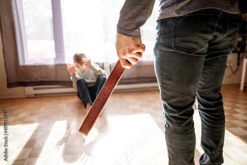 Fototapeta Sad child boy sit on the floor with father in front of him with belt on hand