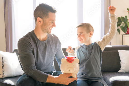 Father with little son with piggy bank at home Fototapete
