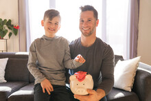Father With Little Son With Piggy Bank At Home