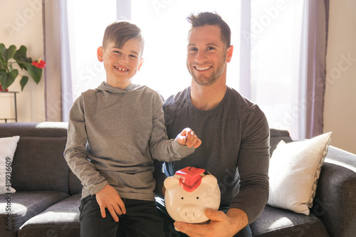 Canvas Print Father with little son with piggy bank at home