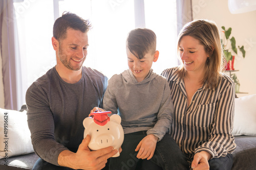 Tela family with little son with piggy bank at home