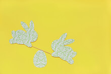 Cute Easter Rabbits Green On A Yellow Background. Decor With Your Own Hands Made Of Paper. Rabbits Swing On Swings