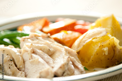 Fototapeta Chicken and potatoes served with vegetables obraz