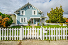 Front View Of A Victorian Style Home With A White Picket Fence, Wraparound Porch And Garden In The Pacific Northwest Of The USA