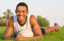 Happy Fit Black Teen Athlete Resting On The Grass With A Rugby Ball. Sports Lifestyle.