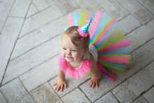 The First Birthday Of The Baby. A Little Girl In A Bright Tutu Skirt With A Gift