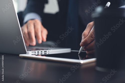 Businessman using touchscreen pen touching on digital tablet screen during working on laptop computer at office