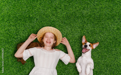 Obraz Laughing girl and cute dog enjoy summer day on the grass - fototapety do salonu