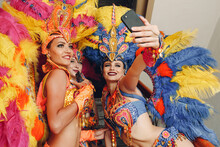 Woman In Brazilian Samba Carnival Costume With Colorful Feathers Plumage With Mobile Phone Take Selfie In Old Entrance With Big Window