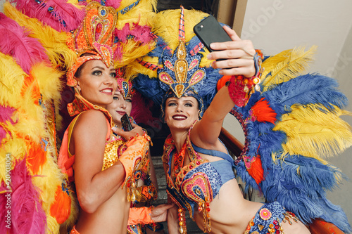 Leinwand Poster Woman in brazilian samba carnival costume with colorful feathers plumage with mo