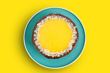 Homemade Chocolate And Orange Cheesecake Sprinkled With Almond Slices On Yellow Background. Top View.