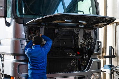 Mechanic repairing the truck in the garage