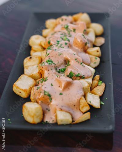 Slika na platnu Racion de patatas bravas españolas con salsa picante