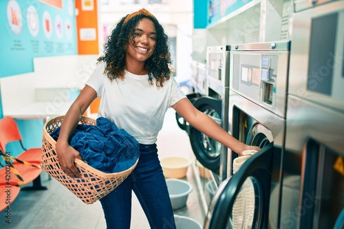 Fotografie, Obraz Young african american woman with curly hair smiling happy doing chores at the l