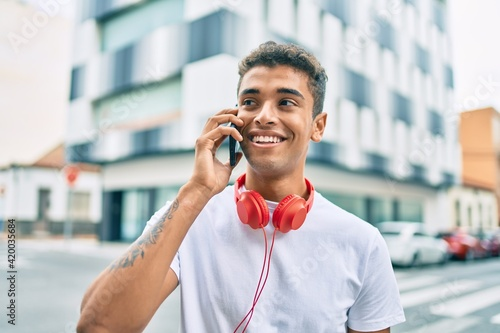 Young latin man smiling happy talking on the smartphone and using headphones at the city Fototapeta