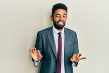 Handsome Hispanic Man With Beard Wearing Business Suit And Tie Disgusted Expression, Displeased And Fearful Doing Disgust Face Because Aversion Reaction.
