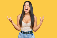 Young Beautiful Hispanic Girl Wearing Casual Clothes Crazy And Mad Shouting And Yelling With Aggressive Expression And Arms Raised. Frustration Concept.