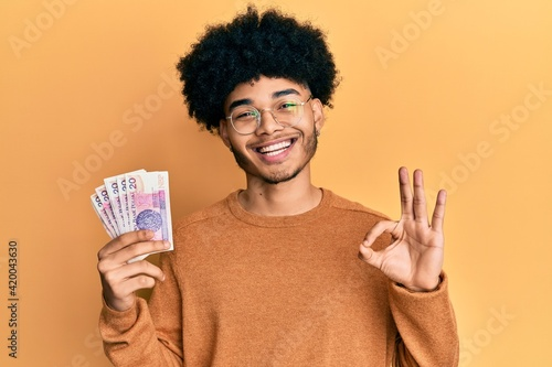 Fototapeta Young african american man with afro hair holding 20 polish zloty banknotes doing ok sign with fingers, smiling friendly gesturing excellent symbol obraz