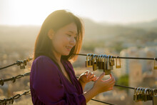 Romantic Lifestyle Portrait Of Young Happy And Beautiful Asian Chinese Woman On Sunset At Love Padlocks Attached To City Railing Smiling Cheerful