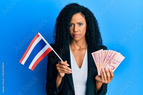 Valokuva Middle age african american woman holding thailand flag and baht banknotes relaxed with serious expression on face