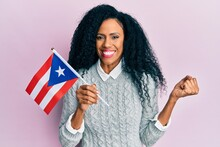 Middle Age African American Woman Holding Puerto Rico Flag Screaming Proud, Celebrating Victory And Success Very Excited With Raised Arm