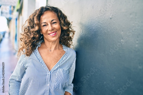 Middle age hispanic woman smiling happy leaning on the wall at the city.