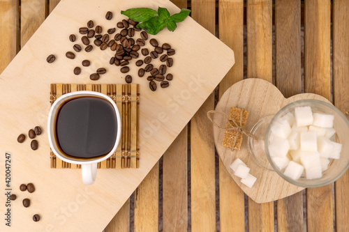 Fototapeta A glass of aromatic coffee and coffee beans in a cozy cafe. Space for your text. obraz