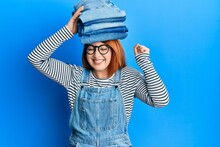 Beautiful Redhead Woman Holding Stack Of Folded Jeans Over Head Screaming Proud, Celebrating Victory And Success Very Excited With Raised Arm