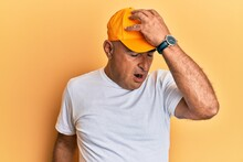 Mature Middle East Man With Mustache Wearing Casual White Tshirt And Yellow Cap Surprised With Hand On Head For Mistake, Remember Error. Forgot, Bad Memory Concept.