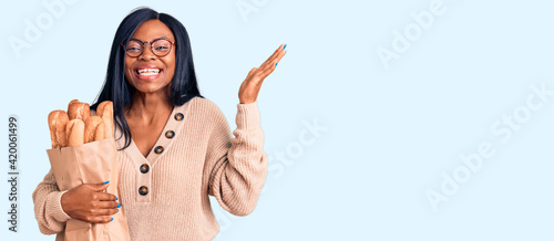 Young african american woman holding paper bag with bread celebrating victory with happy smile and winner expression with raised hands