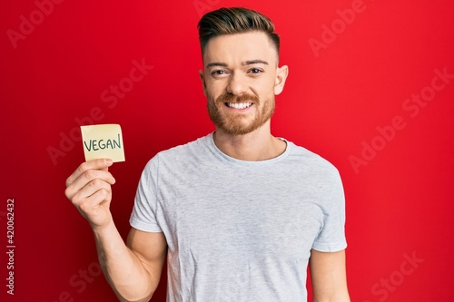 Young redhead man holding sticker with vegan word looking positive and happy sta Fotobehang