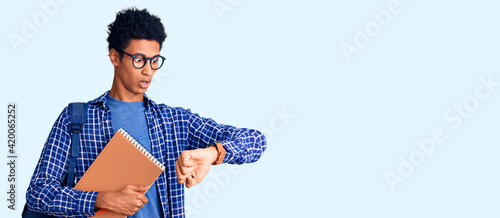 Obraz Young african american man wearing student backpack holding book looking at the watch time worried, afraid of getting late - fototapety do salonu