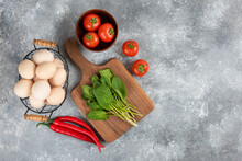 Wicker Basket Of Raw Organic Eggs And Fresh Vegetables On Marble Background