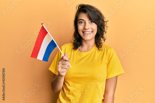 Young hispanic woman holding holland flag looking positive and happy standing and smiling with a confident smile showing teeth