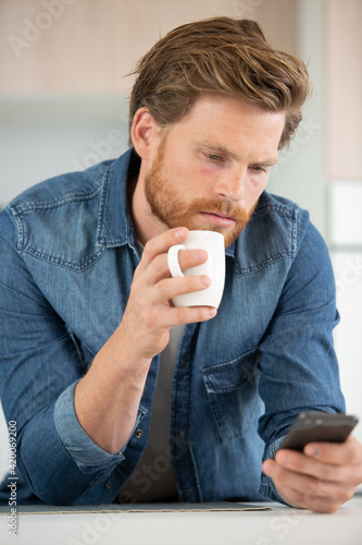 Obraz young man sitting on sofa holding cup while chatting - fototapety do salonu