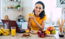 Cute Beautiful And Happy Young Brunette Woman In The Kitchen At Home Is Preparing Fruit Vegan Salad Or A Healthy Smoothie And Having Fun