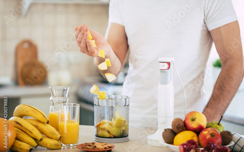 Obraz Handsome young sporty smiling man in the kitchen is preparing vegan healthy fruits salad and smoothie in a good mood - fototapety do salonu