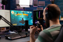 Over Shoulder Footage Of Professional Streamer Playing Digital Videogames On Computer Using Headphones, Microphone And Controle. Streaming Man Raising Hands For Wining Space Shooter Game